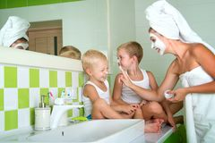 A mãe e as crianças fazem uma máscara protetora na manhã O gracejo dos meninos com mamã fotografia de stock royalty free