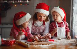 A mãe e as crianças felizes da família cozem cookies para o Natal Fotografia de Stock