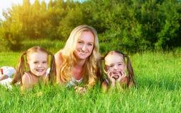 A mãe e as crianças felizes da família juntam irmãs no prado no summe Imagens de Stock