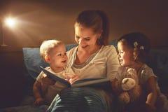 A mãe e as crianças felizes da família leram um livro na cama Fotografia de Stock