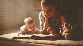 A mãe e as crianças felizes da família leram um livro na noite Imagens de Stock Royalty Free