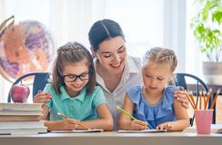 A mãe e as filhas estão aprendendo escrever imagem de stock royalty free