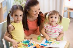 A mãe e as filhas estão pintando junto A família feliz está colorindo com pincel A mulher e as crianças têm um divertimento fotografia de stock royalty free