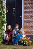 A mãe e as filhas felizes sentam-se no patamar de sua casa fotografia de stock