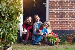 A mãe e as filhas felizes sentam-se no patamar de sua casa imagens de stock royalty free