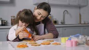 A mãe e as necessidades especiais caçoam a decoração de cookies vídeos de arquivo