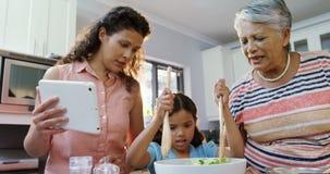 Mãe e avó que ajudam à menina a misturar a salada 4K 4k filme