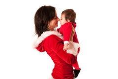 Mãe e bebê ambos como Santa que sorri entre si Fotografia de Stock Royalty Free