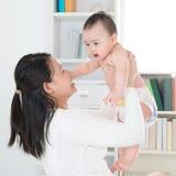 Mãe e bebê asiáticos em casa. Fotos de Stock