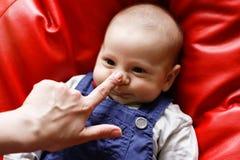 Mãe e bebê com o dedo no nariz imagens de stock