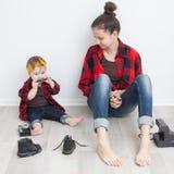 Mãe e bebê em camisas quadriculado e em calças de brim imagem de stock royalty free