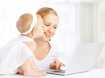 Mãe e bebê em casa que usam o laptop imagem de stock