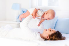 Mãe e bebê em uma cama branca Fotografia de Stock Royalty Free