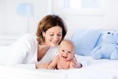Mãe e bebê em uma cama branca Fotos de Stock