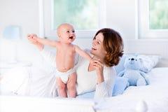 Mãe e bebê em uma cama branca Foto de Stock Royalty Free