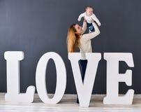 Mãe e bebê felizes do retrato, no fundo cinzento perto das grandes letras do amor da palavra Imagem de Stock Royalty Free