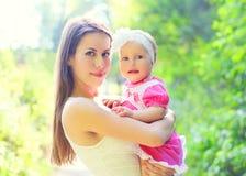 Mãe e bebê novos felizes do retrato nas mãos no verão Imagens de Stock Royalty Free