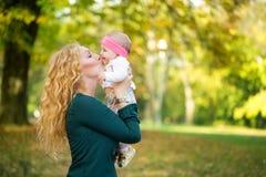 Mãe e bebê que beijam na natureza exterior Fotografia de Stock