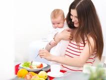 Mãe e bebê que comem em casa Retrato de sorriso feliz da família Imagens de Stock Royalty Free
