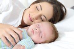 Mãe e bebê que dormem junto na cama Imagens de Stock