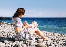 Mãe e bebê que jogam fora na praia do mar imagens de stock royalty free