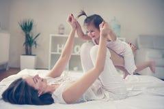 Mãe e bebê que jogam na cama imagem de stock royalty free