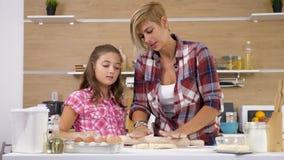 Mãe e cozimento novo da filha e cozimento junto na cozinha video estoque