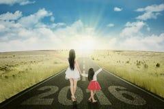 Mãe e criança com números 2016 na estrada Imagem de Stock Royalty Free