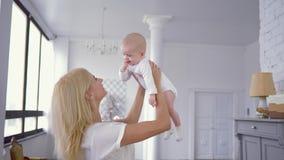 Mãe e criança do relacionamento, jogo alegre da mamã e aumentos acima da cabeça da menina infantil doce com o dedo na boca dentro video estoque