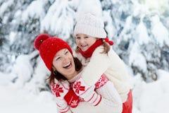 A mãe e a criança em chapéus feitos malha do inverno jogam na neve em férias do Natal da família Chapéu feito a mão e lenço de lã fotografia de stock