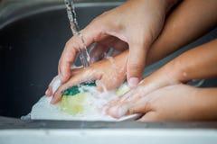 A mãe e a criança entregam pratos de lavagem sobre o dissipador imagem de stock royalty free