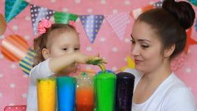 A mãe e a criança estão fazendo uma experiência com espuma colorida Mãos sujas na pintura Cor do estudo para crianças multicolore video estoque