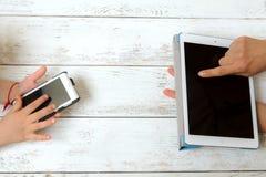 A mãe e a criança estão guardando a tabuleta e um telefone Foto de Stock Royalty Free