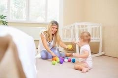 A mãe e a criança estão jogando na sala imagens de stock royalty free