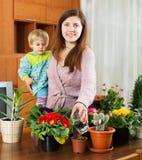 A mãe e a criança estão transplantando e flores em pasta molhadas Imagens de Stock Royalty Free
