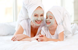 A mãe e a criança felizes da família fazem a máscara da pele da cara imagens de stock royalty free