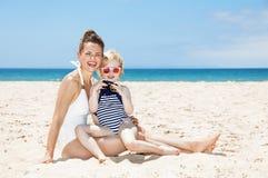 Mãe e criança felizes na praia que olha em fotos in camera Fotografia de Stock