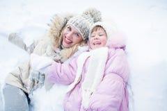A mãe e a criança felizes têm o divertimento na neve no inverno Foto de Stock Royalty Free