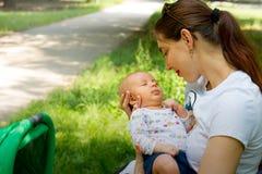 A mãe e a criança, jovem mulher feliz estão guardando seu bebê bonito nas mãos, mãe loving que sorri e que afaga nela recém-nasci imagem de stock