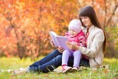 A mãe e a criança leram um livro fora no outono Fotografia de Stock Royalty Free