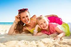 Mãe e criança modernas de sorriso na colocação do litoral imagens de stock