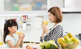 Mãe e criança no suco bebendo da cozinha imagem de stock