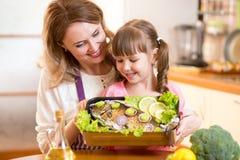 A mãe e a criança olham agradavelmente o prato preparado de Imagem de Stock