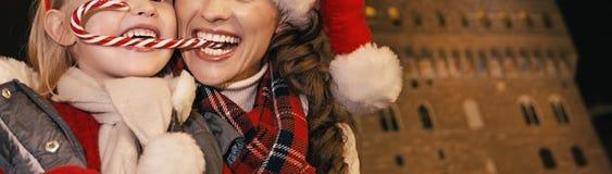 Mãe e criança que comem o bastão de doces do Natal em Florença, Itália Imagens de Stock Royalty Free