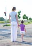 Mãe e criança que cruzam a estrada. imagens de stock royalty free