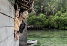 Mãe e criança que olham a janela exterior na vila do mar de Semporna, Sabah Semporna, Malásia imagem de stock