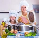 Mãe e criança que preparam a carne Imagens de Stock