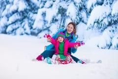 Mãe e criança que sledding em um parque nevado Fotografia de Stock