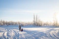 Mãe e criança que sledding no inverno fotografia de stock royalty free