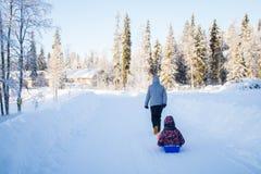 Mãe e criança que sledding no inverno fotografia de stock
